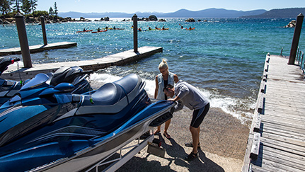 Man and woman unloading jet skis at lake