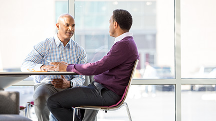 Businessman sitting at a table with a SBDC employee offering small business advice