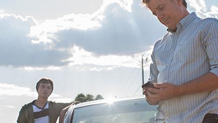 Hombre llamando a asistencia en carretera porque su auto se quedó sin gasolina