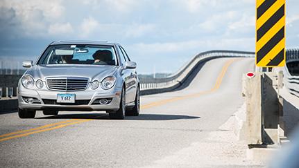Un auto plateado desplazándose por la carretera